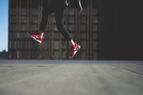person jumping shoes red nike