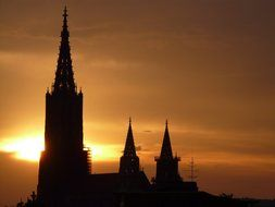 silhouettes of ulm cathedral towers at sunset sky, germany, munich