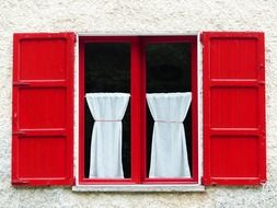window with red wooden shutters and white curtains