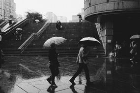 people with umbrellas in rain in wet city