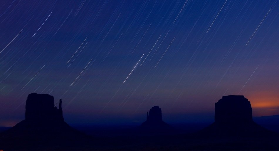 startrails at night sky above monument valley, usa, arizona
