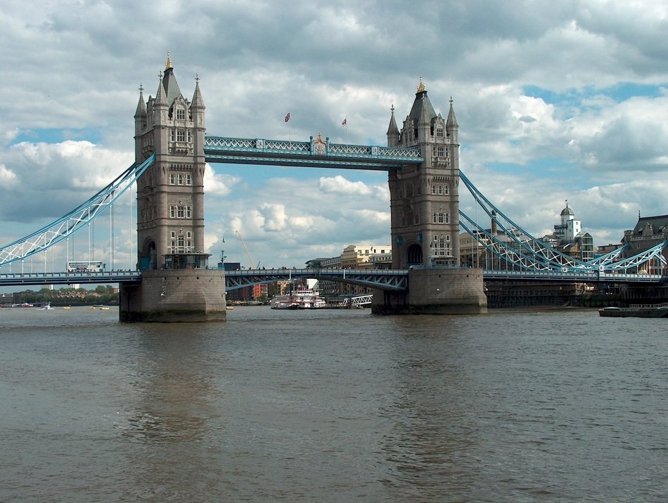tower bridge across thames river at cloudy sky, uk, england, london