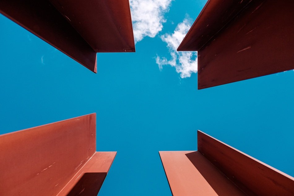 four red metal beams at blue sky
