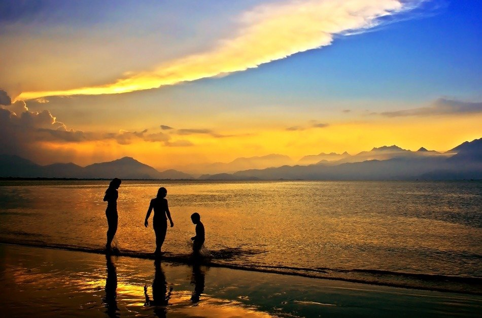 people at sea, colorful sunset above calm bay, vietnam, da nang