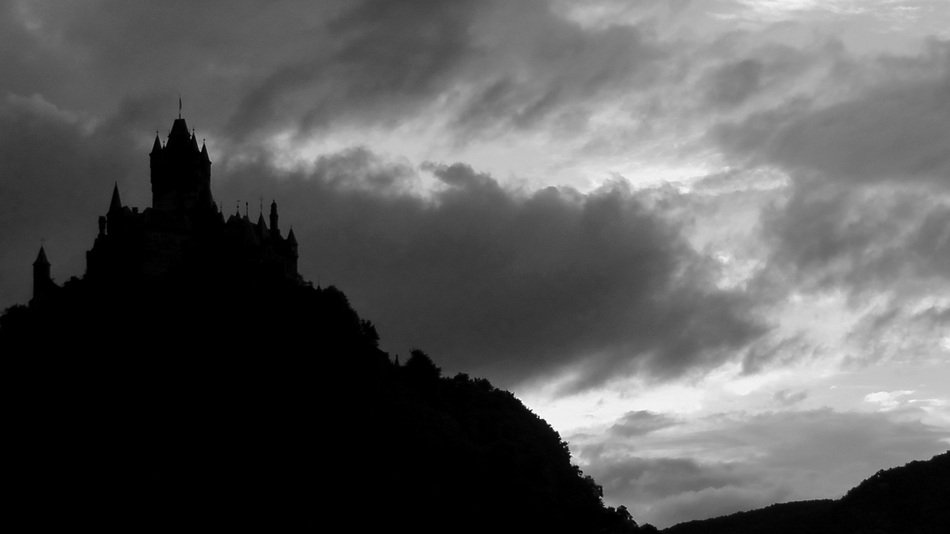 castle on top of mountain, silhouette at clouds