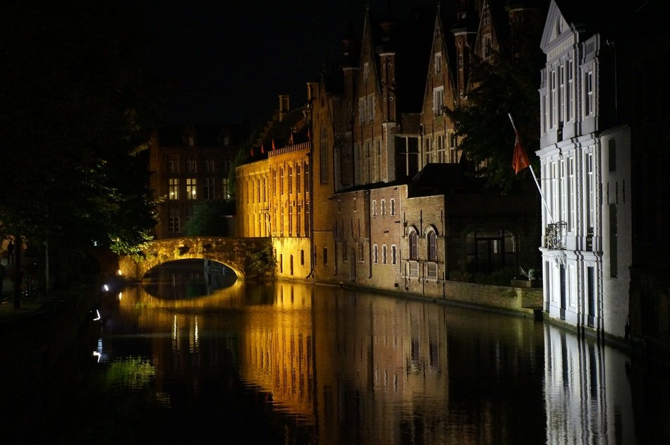 illuminated old buildings and bridge mirroring on canal at night, belgium, bruges
