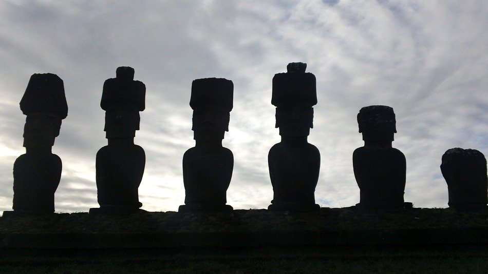 moai statues, dark silhouettes at cloudy sky, easter island