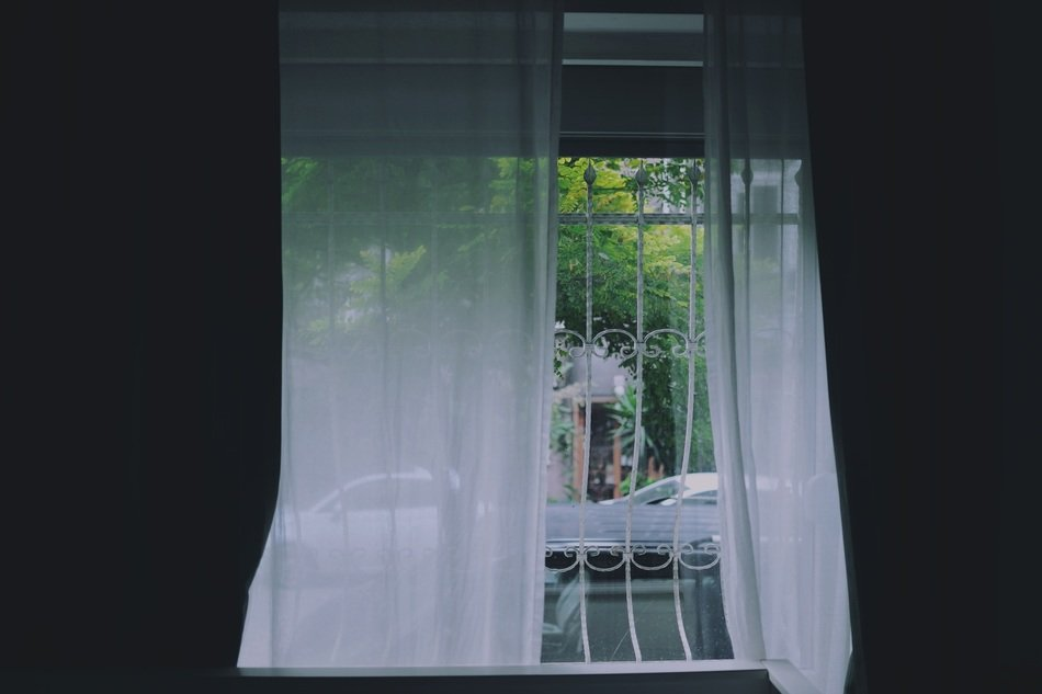 white curtains on grated window