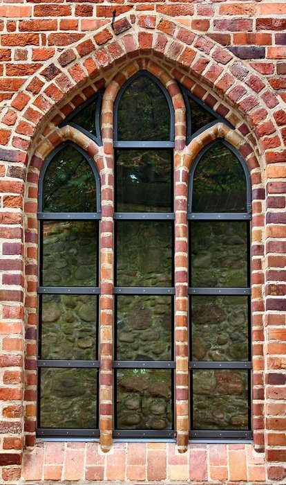 grated arched window in red brick wall