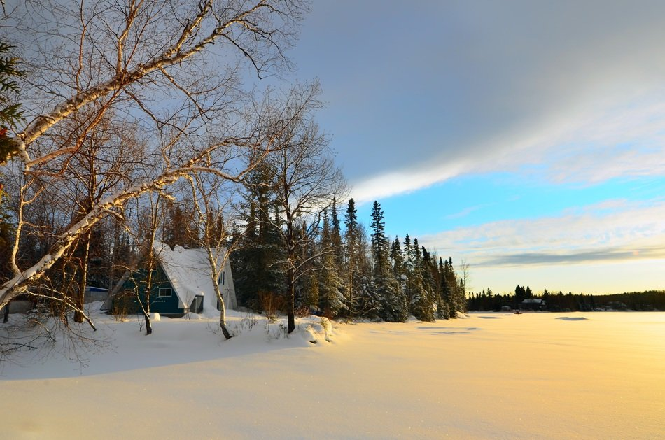 snowy winter landscape with birch and hut at frozen lake