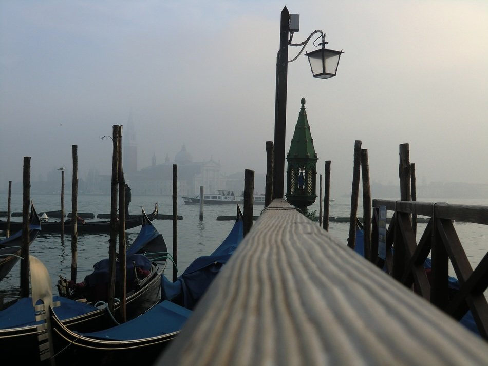 gondolas at pier in foggy cityscape, italy, venice