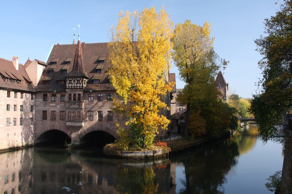 autumn landscape with medieval hospital building at water, germany, nuremberg