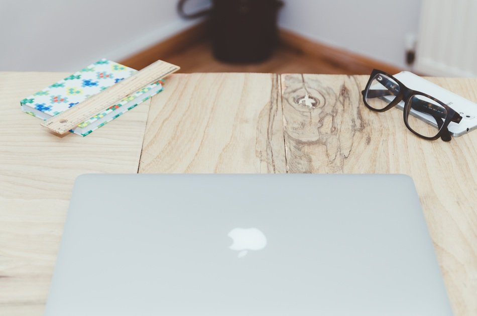 apple laptop and glasses on desk