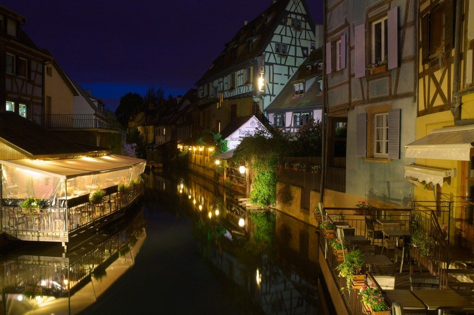 beautiful old buildings with waterside terraces at night, france, alsace, colmar