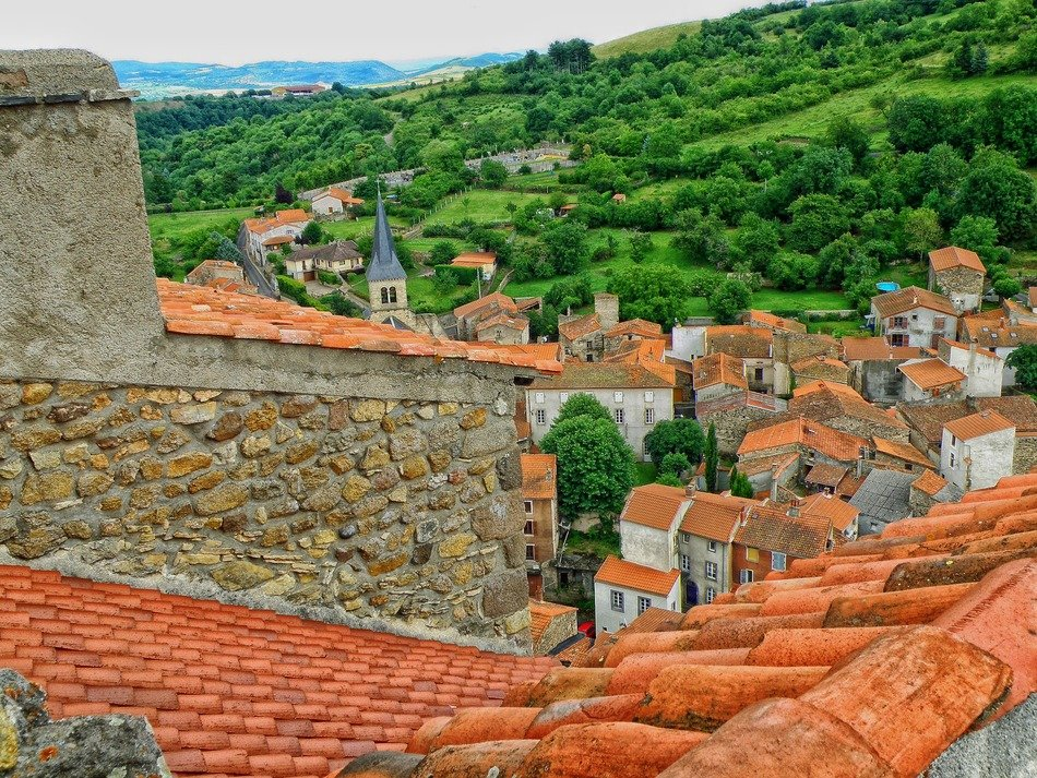 old town with red clay tile roofs in picturesque landscape, france, champeix
