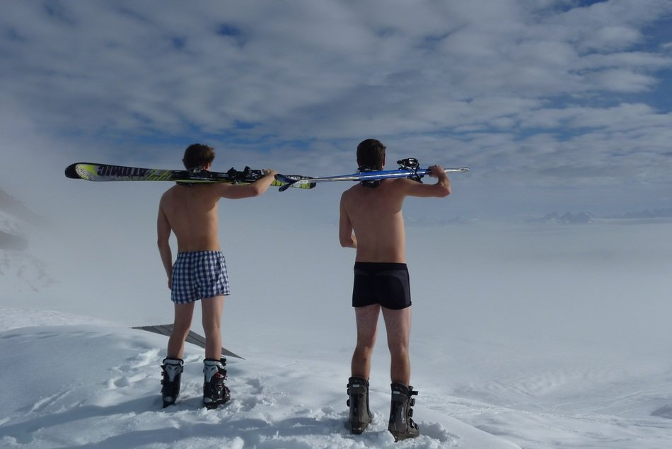 back view of two young men with skis on snowy mountain at sky