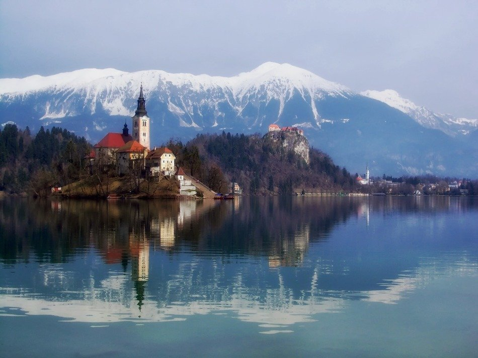 castle in forest at snow-capped mountains on landscape, slovenia, Bled Island