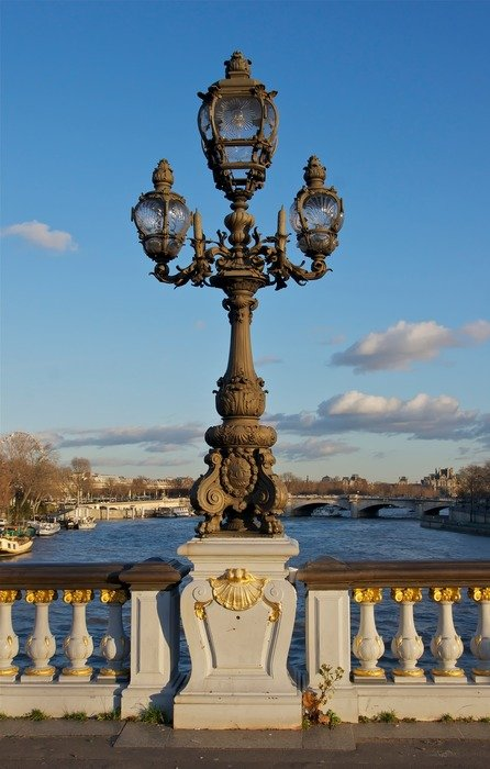 antique lamp post on bridge across river, france, paris