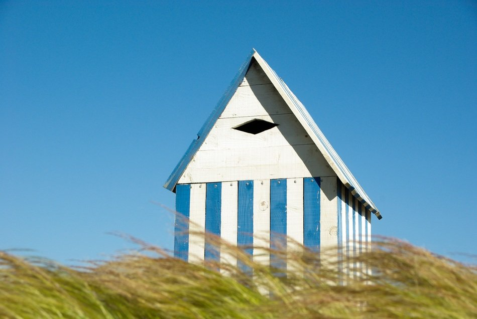 striped wooden beach cabin behind tall grass at blue sky