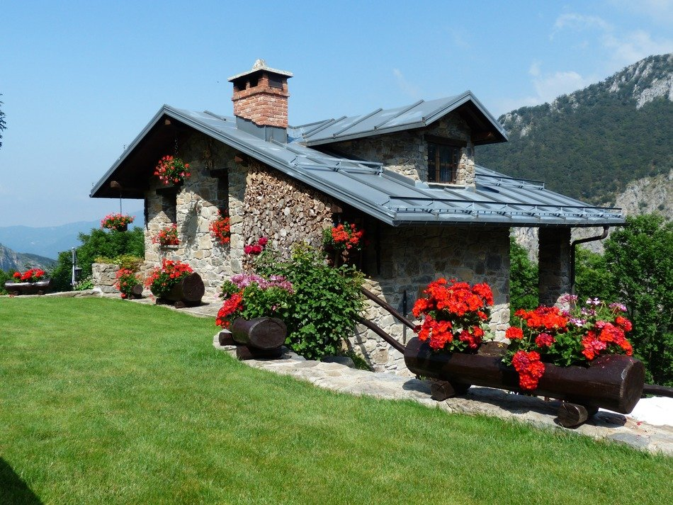 small beautiful holiday house, decorated with red flowers, at mountains