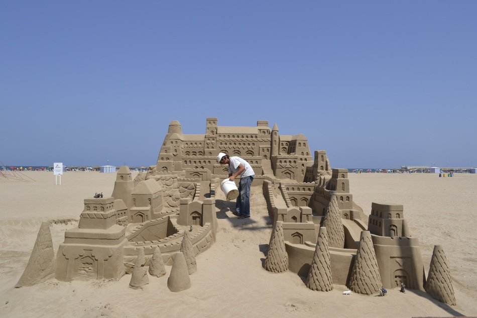 man is building sand castle on beach