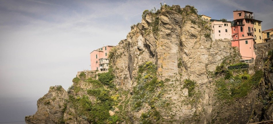 pink houses on cliff at cloudy sky, italy, cinque terre