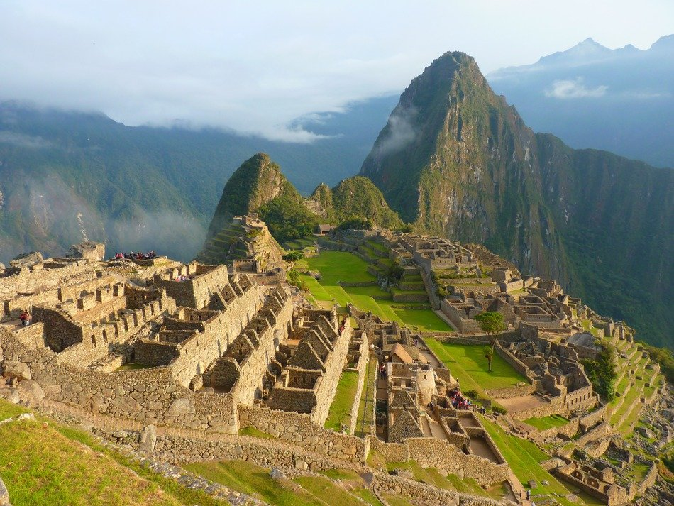 machu picchu, inca town ruins on green mountain under clouds, peru