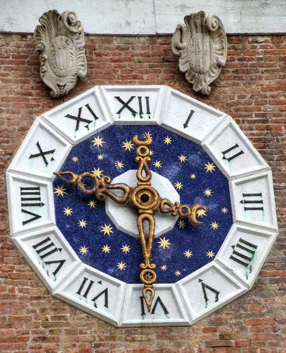 old clock with golden stars on brick wall