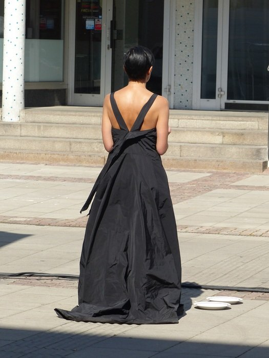 back view of woman in long black dress on street at building