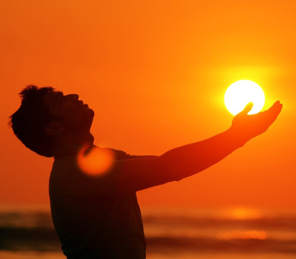 man silhouette with sun on hand at sunset sky