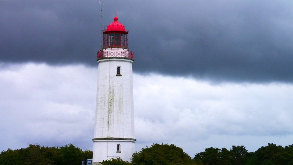 lighthouse with red top at grey clouds