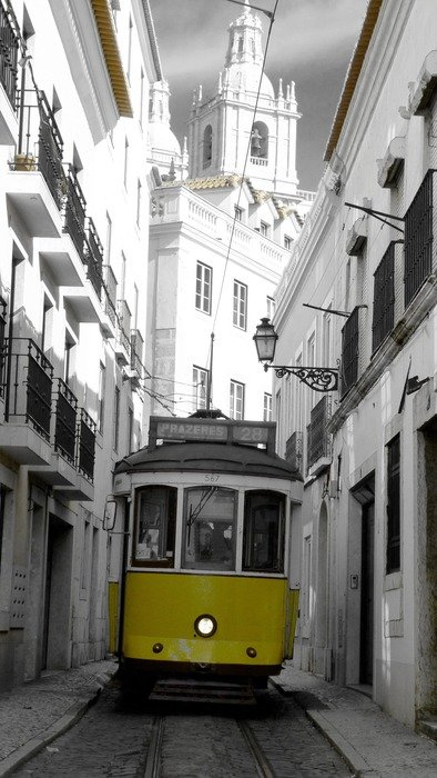 yellow tram on narrow street in old town, portugal, lisbon