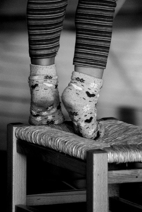 child's feet in socks on chair