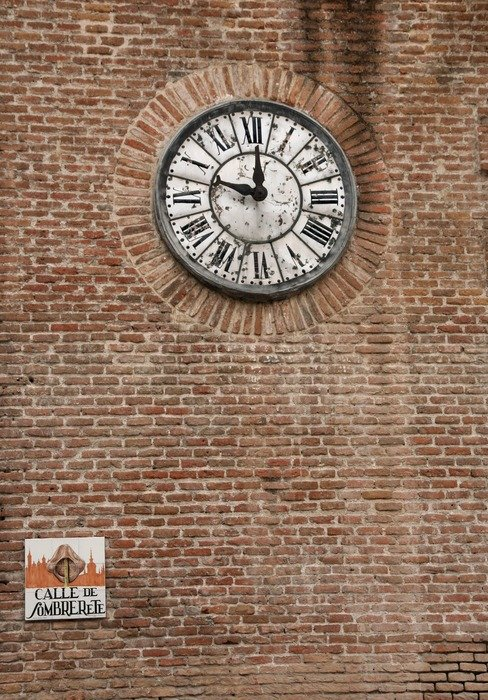 antique clock on red brick wall, spain, madrid