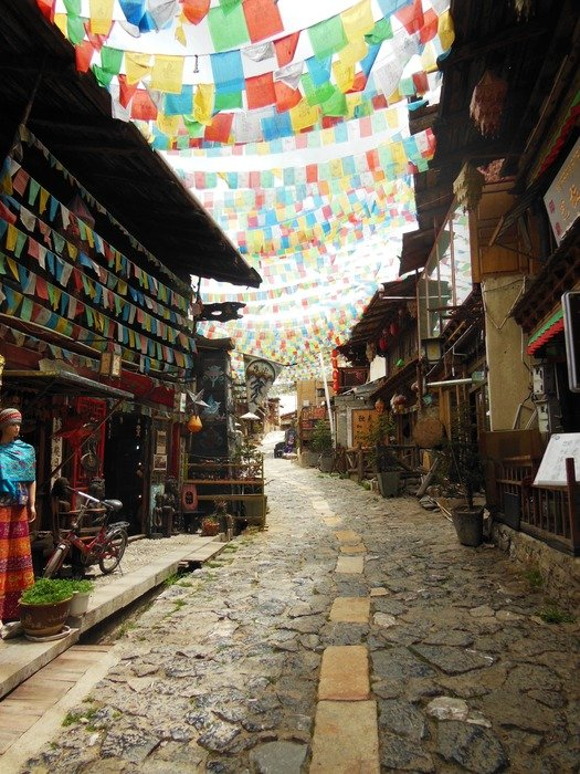 colorful prayer flags on lines across street, china, yunnan, shangri la