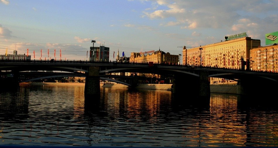 old bridge across river in city at evening