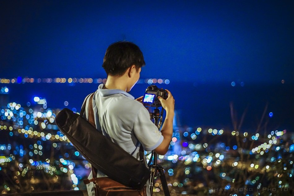 back view of photographer taking pictures above night city