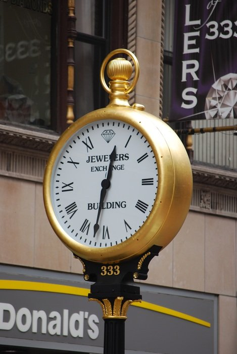 vintage golden street clock on pole