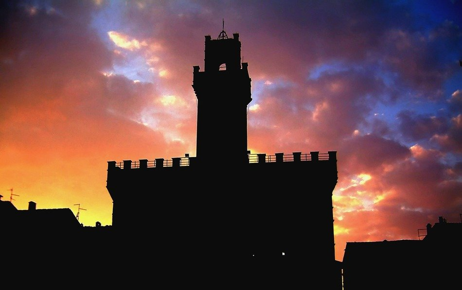 dark silhouette of medieval castle at colorful sunset sky
