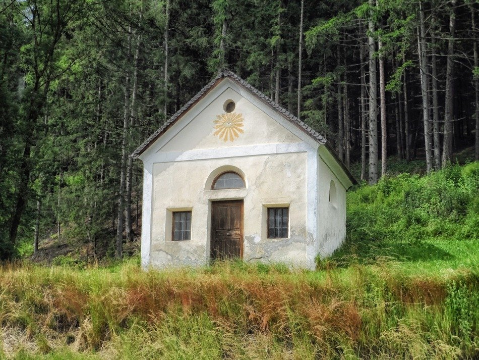 small white chapel at summer forest, austria