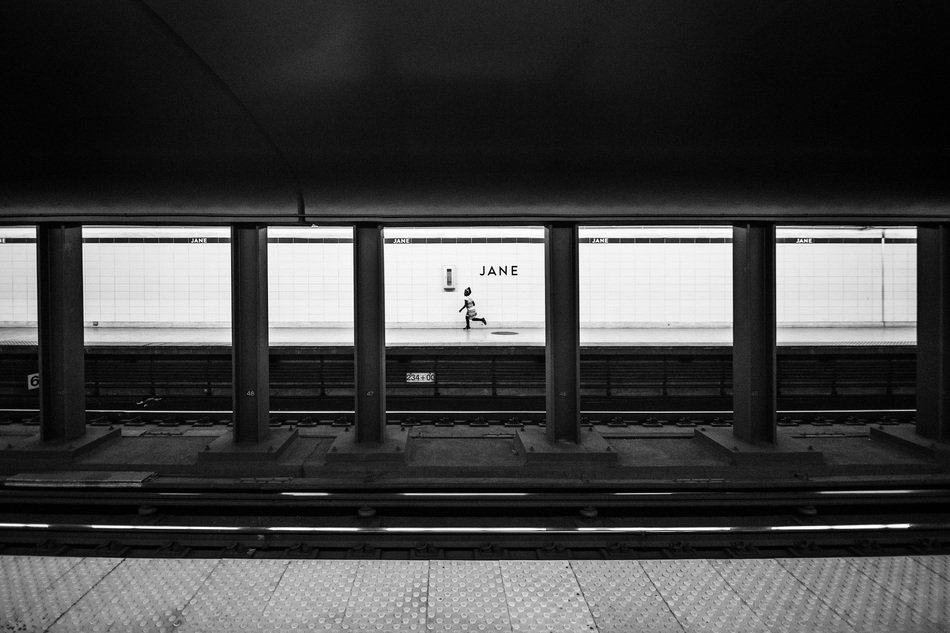 child running on platform of subway station