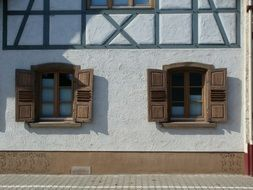 windows with brown shutters on truss house facade
