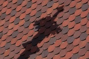 Shadow of a cross on a tiled roof