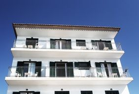 house apartments white balcony building blue sky