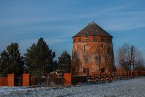 old red windmill in rural winter landscape