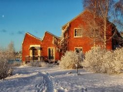red brick house in snowy winter landscape, finland