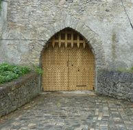 closed gates with grate in medieval stone wall