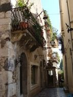 old alley with plants on balconies, italy, sicily, taormina