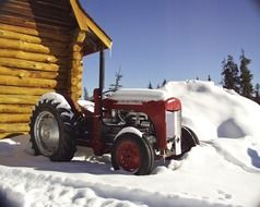 red tractor near log building at snowy winter