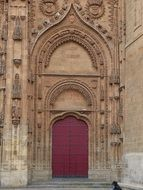 closed red door of cothic church, spain, salamanca